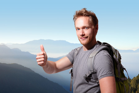 happy man mountain hiker with backpack and show thumb up on the top of mountains. caucasian photo