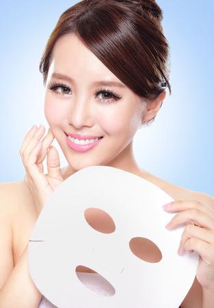 limpieza de cutis: feliz mujer joven con el paño máscara facial aislado en azul, el concepto de cuidado de la piel, asiático