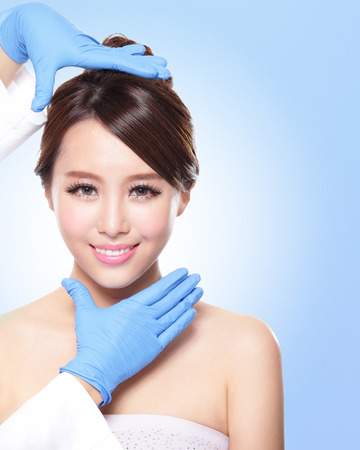plastic glove: Plastic surgery touching the head of a beautiful female face, concept for micro plastic surgery, asian beauty Stock Photo