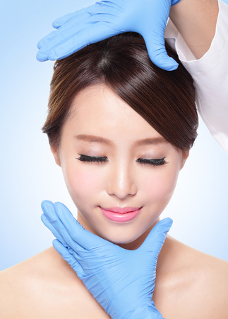 Plastic surgery touching the head of a beautiful female face photo