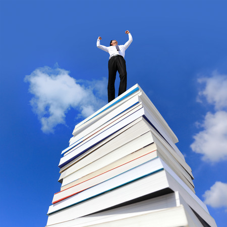 arise: Knowledge is power, Excited business man arise arm cheering and celebrating on a stack Of Books