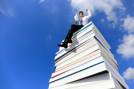 knowledge is power: Knowledge is power - Happy business man using tablet pc computer and sitting on a stack Of Books Stock Photo