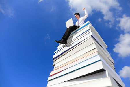 Knowledge is power - Happy business man using pc computer and sitting on a stack Of Books photo