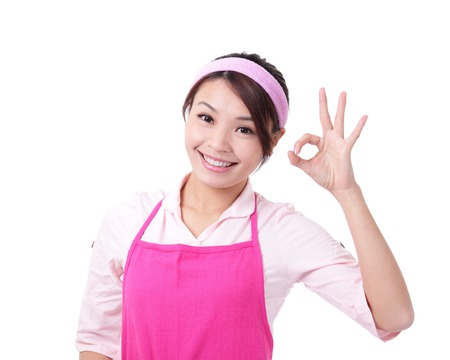 Happy young woman housewife mother wearing kitchen apron and showing OK, asian