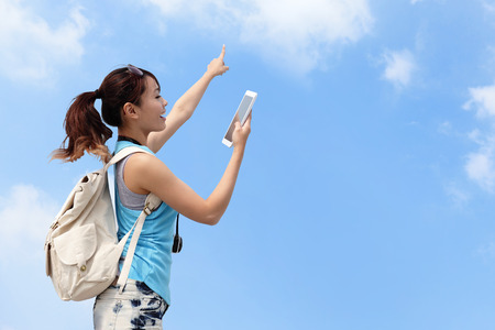 Happy woman traveler use tablet pc with sky background photo