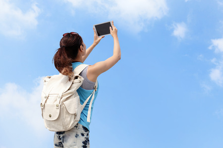 Happy woman traveler photo by tablet pc with blue sky photo