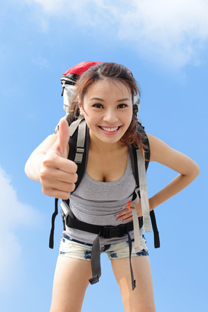 extreme angle: happy woman mountain hiker show thumb up with sky background. asian