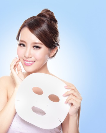 happy Young woman with cloth facial mask isolated on blue background, concept for skin care, asian Stock Photo