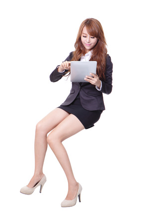 Happy business woman sitting on something and using tablet pc isolated against white background, asian beauty photo
