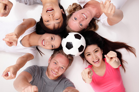 Happy Group of friends with soccer lying and making a circle, asian and caucasian photo