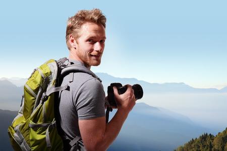 コーカサス山の上に写真を撮るバックパックと若い男