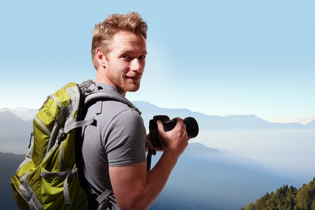 picture person: Young man with backpack taking a photo on the top of mountains, caucasian
