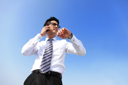 phone the clock: business man look watch with blue sky