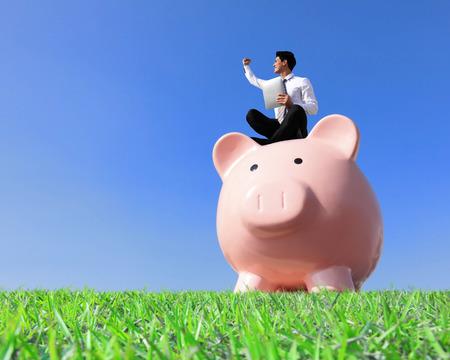 einsparung: Glückliche Geld sparen mit meinem Sparschwein - Junger Geschäftsmann sitzt auf Sparschwein mit Touchpad Lizenzfreie Bilder