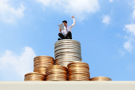 Successful business man working and using tablet pc on growth money stairs coin with sky photo