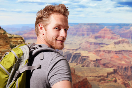 happy young people: Grand Canyon travel  - Successful man mountain hiker with backpack on the top of mountains. caucasian Stock Photo