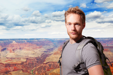 Grand Canyon travel  - Successful man mountain hiker with backpack on the top of mountains. caucasian photo