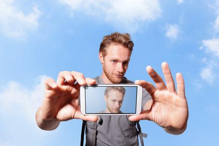 profil: gl�cklicher Mann durch intelligentes Telefon mit Himmel Hintergrund, kaukasisch selfie