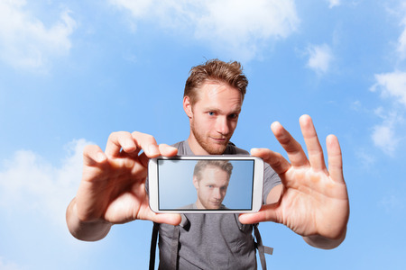 nature picture: happy man selfie by smart phone with sky background, caucasian