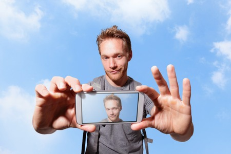 happy man selfie by smart phone with sky background, caucasian photo