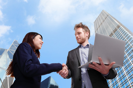 business people shaking hands with city background photo
