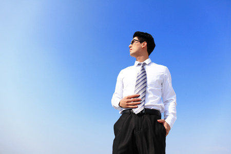 Successful handsome business man purposefully looking away with blue sky photo
