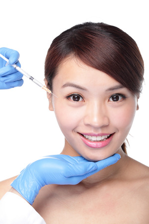 Close up of cosmetic injection to the pretty woman face. Isolated on white background, asian photo