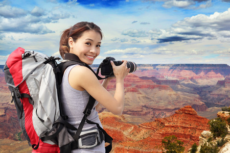 Young woman with backpack taking a photo in grand canyon, asian photo
