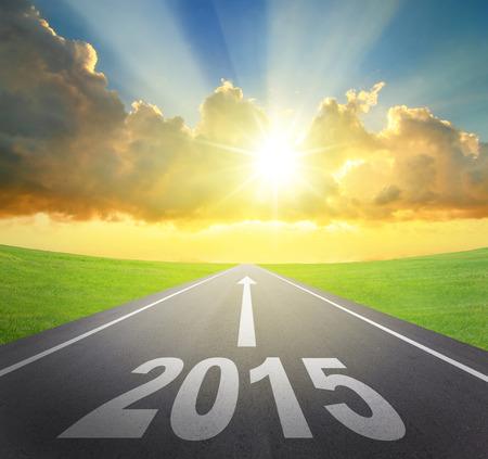 new Year: Inoltra al 2015 concetto nuovo anno, strada asfaltata con freccia, data e bel tramonto e il sole