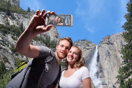 happy couple selfie by smart phone in yosemite national park, caucasian photo