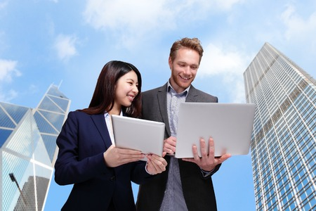 Business meeting - two managers discussing on tablet computer with city background photo
