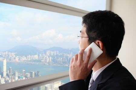 Young business man talking on smart phone in office and look city through window, asia, hong kong, asian photo