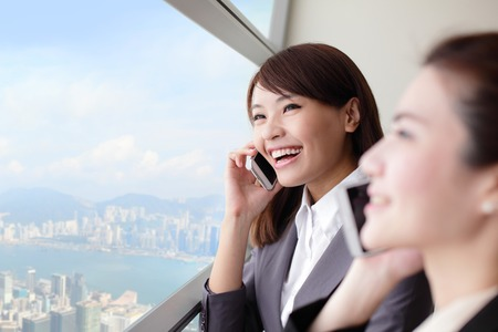 Smile Business woman speaking phone and looking through window with city background, asia, hong kong, asian photo
