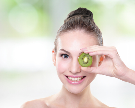 wellfare: Beautiful woman face with kiwi fruit with nature green background, caucasian Stock Photo