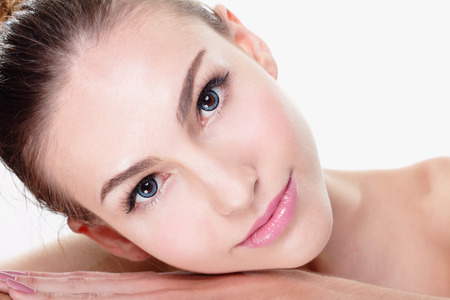 beauty care: Close up portrait of beautiful young woman face while lying. Isolated on white background. Skin care or spa concept, caucasian