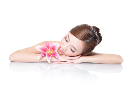 sexy asian girl: Beautiful face skincare beauty woman lying down with pink lily flower amd mirror reflection isolated on white background. asian beauty