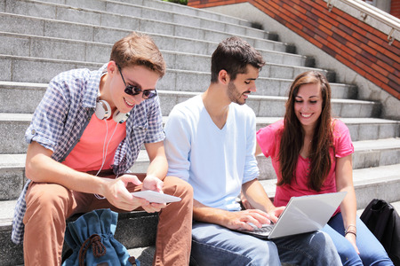 college student: Happy students sitting on stairs using digital tablet and conservation to each other in school, caucasian