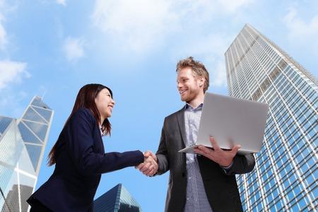 stretta di mano: uomini d'affari si stringono la mano con sfondo di città
