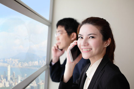 Smile Business team speaking phone and looking through window with city background, asia, hong kong, asian photo