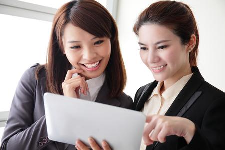 reuniones empresariales: Mujeres de negocios que miran y sonr�en conversaci�n con la tableta digital en la oficina, asi�tico