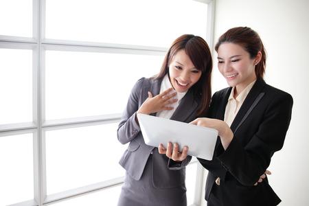 affari: Business donne guardano e sorridono conversazione con tavoletta digitale in Office, asiatico