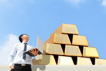 lingotes de oro: Exitoso hombre de negocios mira al crecimiento de lingotes de oro con el cielo Foto de archivo