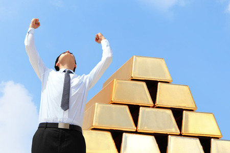 gold bullion: Successful excite business man standing with gold bullion