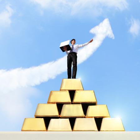 lingotes de oro: Exitoso hombre de negocios que trabaja en el crecimiento de lingotes de oro con el cielo Foto de archivo