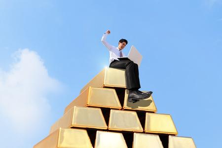 goldbars: Successful business man working on growth gold bullion with sky