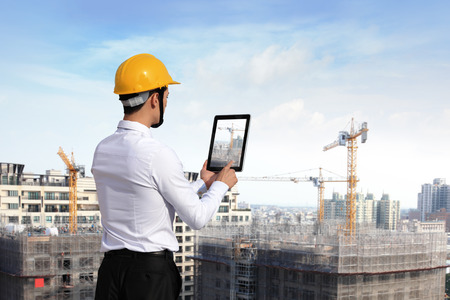 Vista trasera del arquitecto mirando Tablet PC y la comparación con la construcción de viviendas Foto de archivo
