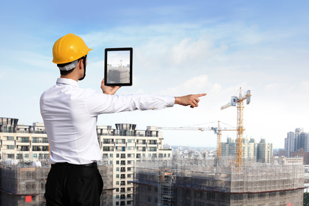 Rear view of architect looking tablet pc and comparing housing project with building