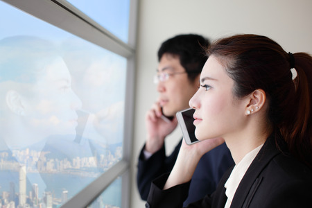woman on cell phone: Business team speaking phone and looking through window with city background, asia, hong kong, asian Stock Photo