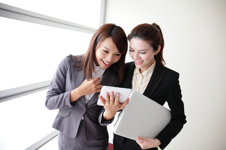 Business women look and smile conversation with computer and digital tablet in Office, asian photo