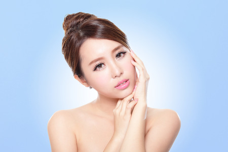 woman hands up: close up of attractive Skin care woman face with blue background, asian